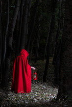 Attractive Woman Dressed A Little Red Riding-hood Walk In A Dark Forest With Lantern
