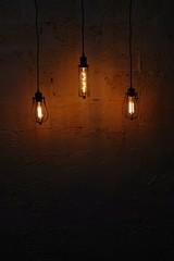Illuminated Light Bulbs Hanging Against Wall In Darkroom