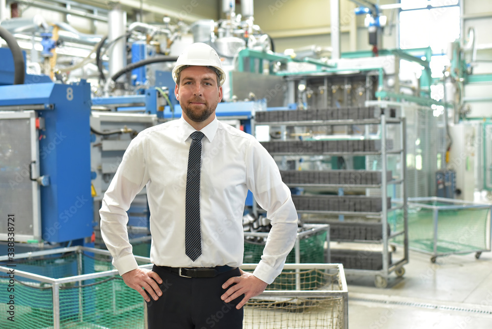 Fototapeta portrait of a successful smiling businessman/ engineer on site in an industrial factory with helmet