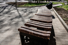 Old Broken Wooden Bench With Peeling Paint In The Park. Poor Attitude To Urban Property. A Place For Walking And Relaxing.