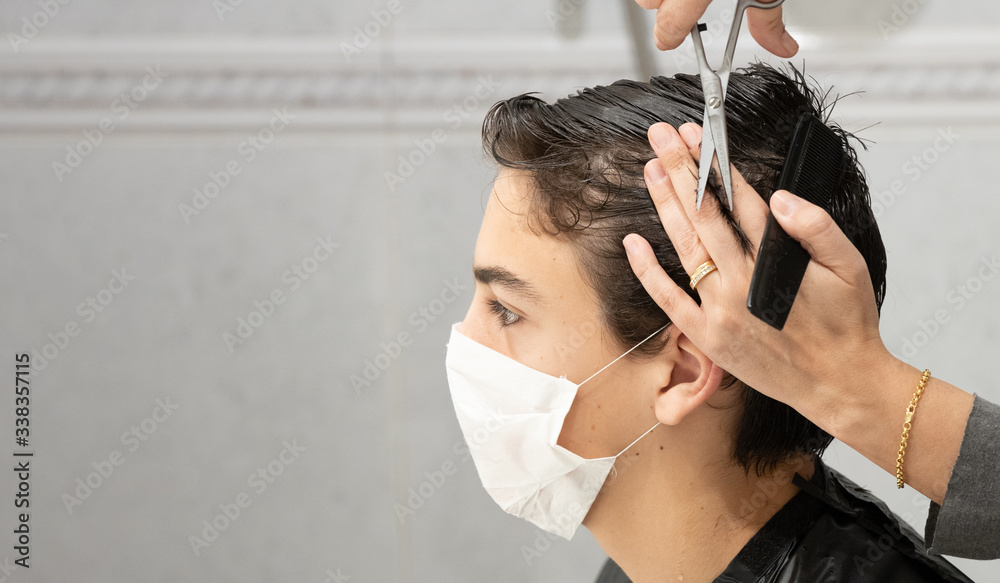 Fototapeta Son with profile facial mask while his mother cuts his hair at home