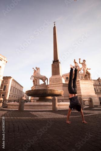 Fototapeta Joven haciendo el pino en plaza de Roma.