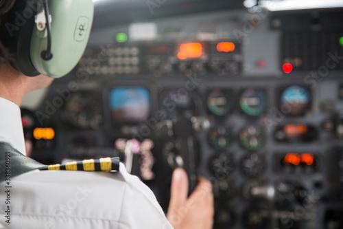 Billede på lærred Midsection Of Pilot Controlling Cockpit In Airplane