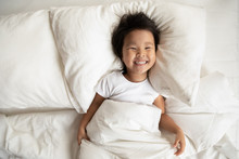 Top View In Bed Fresh Sheets Comfortable Mattress Soft Pillow White Bedding Lies Small Asian Girl Has Wide Charming Toothy Smile Looks At Camera, Kid Woke Up, Enough Healthy Sleep, Feels Active Lively