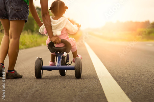 Fényképezés A picture of the warmth of a mother who is teaching her child to ride a bicycle,