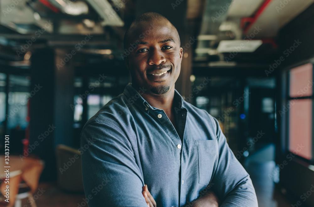 Fototapeta Confident businessman standing in office
