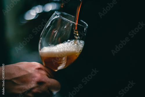 Tela bartender hand at beer tap pouring a draught beer in glass serving in a restaura