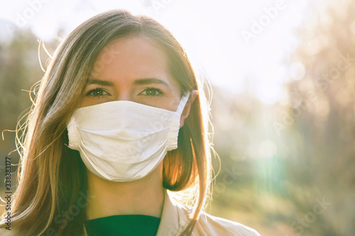 Young woman wearing white cotton virus mouth nose mask, nice backlight sun bokeh Fototapet
