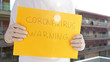 Person with surgical gloves holding yellow sign with coronavirus warning, Covid-19 pandemic.