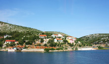 View Of The Shore Of A Lake, River, Sea With Beautiful Small Houses. Houses With Red Roofs, European Places For Tourism. Beautiful Panoramic View Of The Birch From The Boat.
