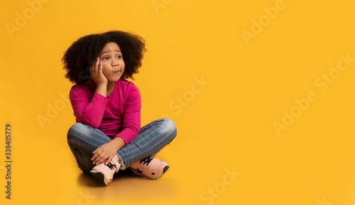 Fototapeta Pensive little girl sitting on floor over yellow background and thinking obraz