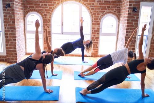 Cuadros en Lienzo Young beautiful group of sportswomen practicing yoga