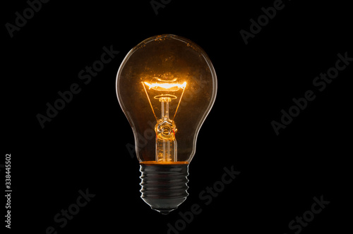 Old, dirty light bulb close up on black background Fototapeta