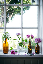 Old Window And Window Sill Decorated With Vintage Bottles And Roses