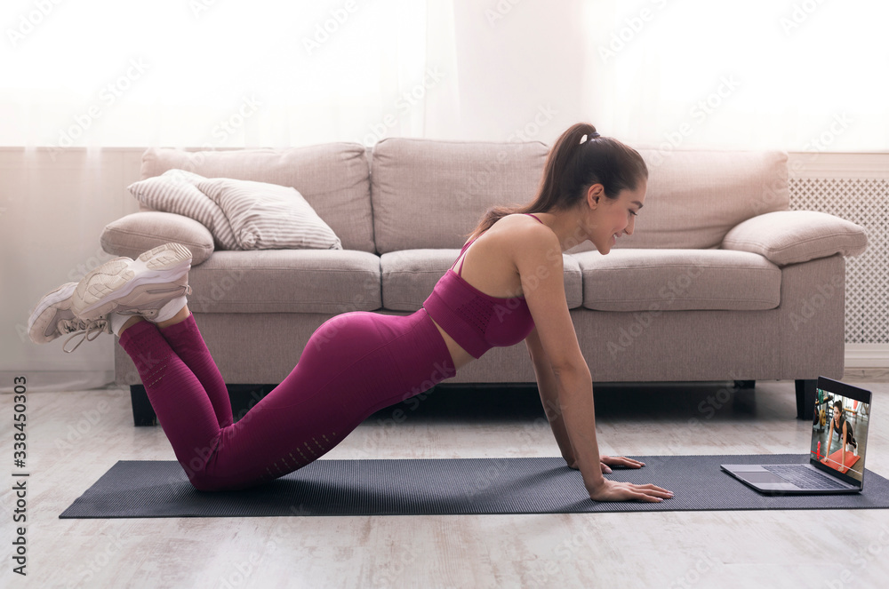Fototapeta Online sport class. Young girl doing exercises, following video tutorial on laptop indoors