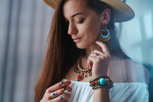 Portrait Of Sensual Brunette Boho Chic Woman Wearing White Blouse And Straw Hat With Earrings, Bracelets, Necklace And Rings. Fashionable Hippie Gypsy Bohemian Outfit With Jewelry Details