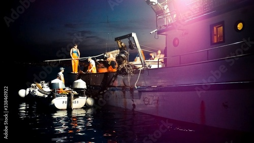 Photo Motorboat And Fishing Trawler At Night