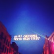 Low Angle View Of Illuminated Christmas Message Hanging Amidst Building Against Clear Sky At Night
