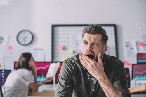 Obraz Selective focus of data analyst yawning in office - fototapety do salonu