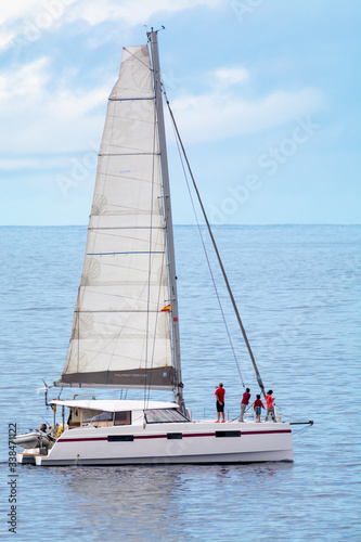 Fotomural Seascape with one sail boat, cloudy sky and waves of Atlantic ocean