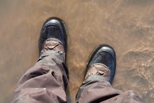 A Pair Of Feet Wearing Hard Solid Hiking Boots Walking In Water From Above. Waterproof Footwear For  Trekking Through Mountains And Rivers. Exercise For Mental Health And Physical Well Being.
