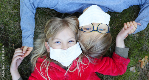 Papel de parede girl and boy lie on the grass in a facial mask during the coronavirus pandemic