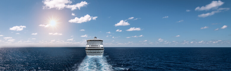Sailing cruise ship on the sea. Rear end of the vessel with a track of foam. Sunset view. Wide panoramic picture.