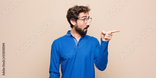 Photo young handsome man feeling shocked and surprised, pointing and looking upwards i