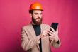 Leinwanddruck Bild - Portrait of happy architect working on tablet over pink background