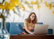 Charming beautiful young girl in glasses with curly hair sits on a blue sofa at home in front of a laptop, remote work and education, beauty and fashion.