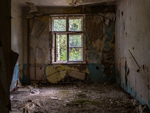 An Abandoned Room With Dirty Walls, Broken Window And Trash On The Floor, A Sunny Forest On The Outside