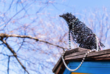 Handmade Crow, Raven Or Magpie On Rooftop. The Bird Is Made Out Of Black Wire And Jewelry (pearl Necklace). It's Sitting On Roof Shingles With Blue Siding. Soft Cherry Tree Background. Folk Art.