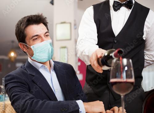 Stampa su Tela Waiter pouring wine to a masked customer, funny coronavirus concept