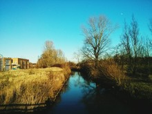Stream With Houses Against Clear Blue Sky