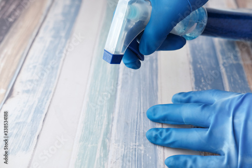 Obraz hand in blue rubber glove holding cleaning cloth and and spray bottle. - fototapety do salonu