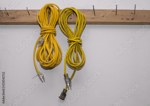 Fototapeta Two yellow electrical extension cords hanging in a workshop.