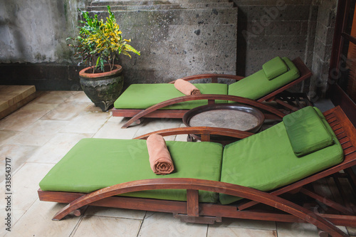 Canvas-taulu Wooden sunbeds next to a swimming pool in beautiful, green, Spanish garden on a sunny day