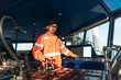 Filipino deck Officer on bridge of vessel or ship wearing coverall during navigaton watch at sea . He is maneuvering with cpp thrusters propulsion