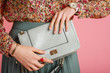 Trendy small green mint color faux leather bag, stylish white wrist watch, beautiful rings. Elegant outfit.  Women`s fashion concept. Copy space