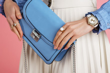 Close Up Of Fashionable Elegant Woman`s Outfit: Trendy Small Blue Faux Leather Bag, Stylish Wrist Watch, Beautiful Rings