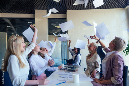Fototapety, obrazy: multiracial group of young women editor of famous magazine collaborating throwing paper up documents in open space office in a modern office with panoramic windows