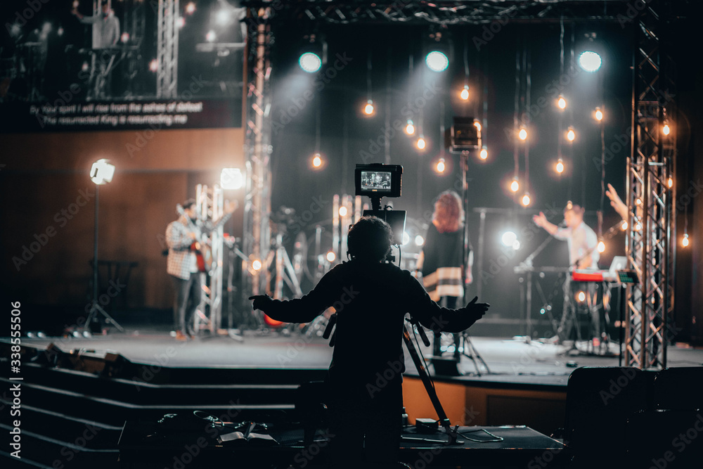 Fototapeta Camera Operator worshipping with the praise band for online church