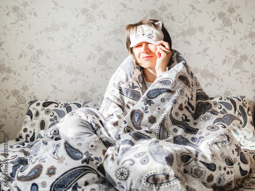 Obraz Young woman in grey pajama and sleeping mask in shape of cute sleeping cat face. She is just woke up and sit in bed. Early morning in cozy home. - fototapety do salonu