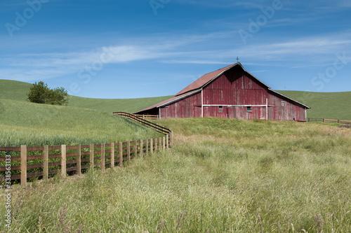 Obraz na plátně A fence leads through the green fields to a sprawling red barn