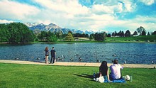 Rear View Of People Relaxing Near Lake