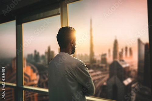 Fototapeta Arabic business man looking out through the office balcony seen through glass window. arab young man looking at Dubai city through hotel window. obraz