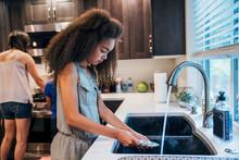 Girl Washing Dishes At Kitchen...
