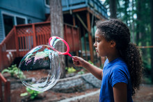 Girl Blowing Giant Bubbles In ...