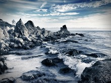Rocky Shore By Sea Against Sky