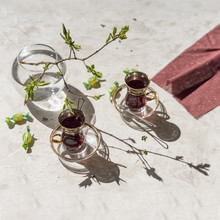Spring Sunny Morning, Cups With Fruit Tea, Napkin And Young Tender Tree Branches, Openwork Shadows On The Table